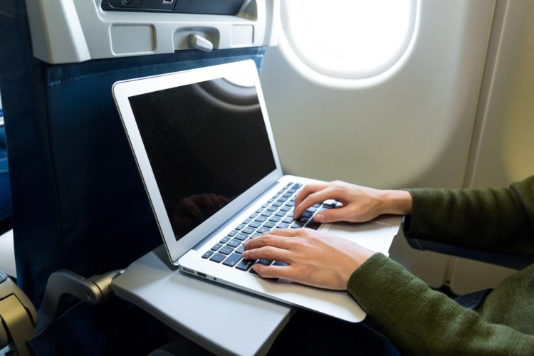 A Travel writer works on their laptop on a plane